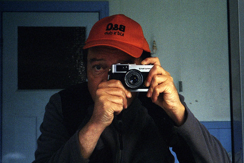 reflected self-portrait with Olympus Trip 35 camera and B&Q Kids Club cap by pho-Tony