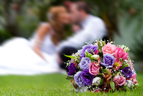 A blurred photo of a bride and groom on the grass with a bouquet in clear view.
