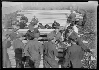 `Pine table' in use at CCC Camp. The lumber on which these boys are having their noon meal will be used to build the barracks which they will occupy this winter, November 1933