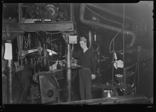 A worker running a Lynch bottle machine. This is an older machine than the I. S, March 1937