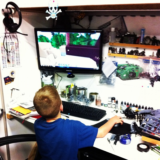 The kid showing me what he was building in #MineCraft earlier today. There is so much going on in this picture. Not my desk.