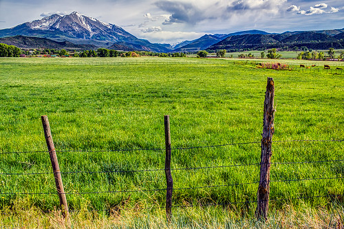sky mountains green field grass clouds america fence landscape rockies outdoors evening landscapes spring scenery colorado view unitedstates farm country peak rockymountains agriculture rugged scenics