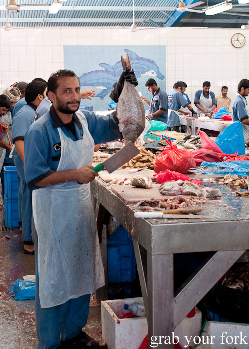 Fishmonger filleting fish inside Dubai Fish Market in Deira