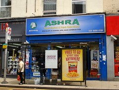 "A blue shopfront with the words ""Ashra / Super Market & Fresh Halal Meats / Specialists in Ghanian, Afro, Asian Caribbean Food"".  In front of the shop is a bus stop with two adverts on it - ""Croydon Council / Cleaner, Safer, Greener"" and ""Fries to go without going anywhere / McCain French Fries / It's all good."" Two people are standing at the bus stop."