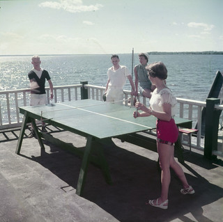 Two men and two women play ping-pong at Britannia Yacht Club, Ottawa, Ontario / Deux hommes et deux femmes jouent au ping-pong au Britannia Yacht Club, à Ottawa, en Ontario
