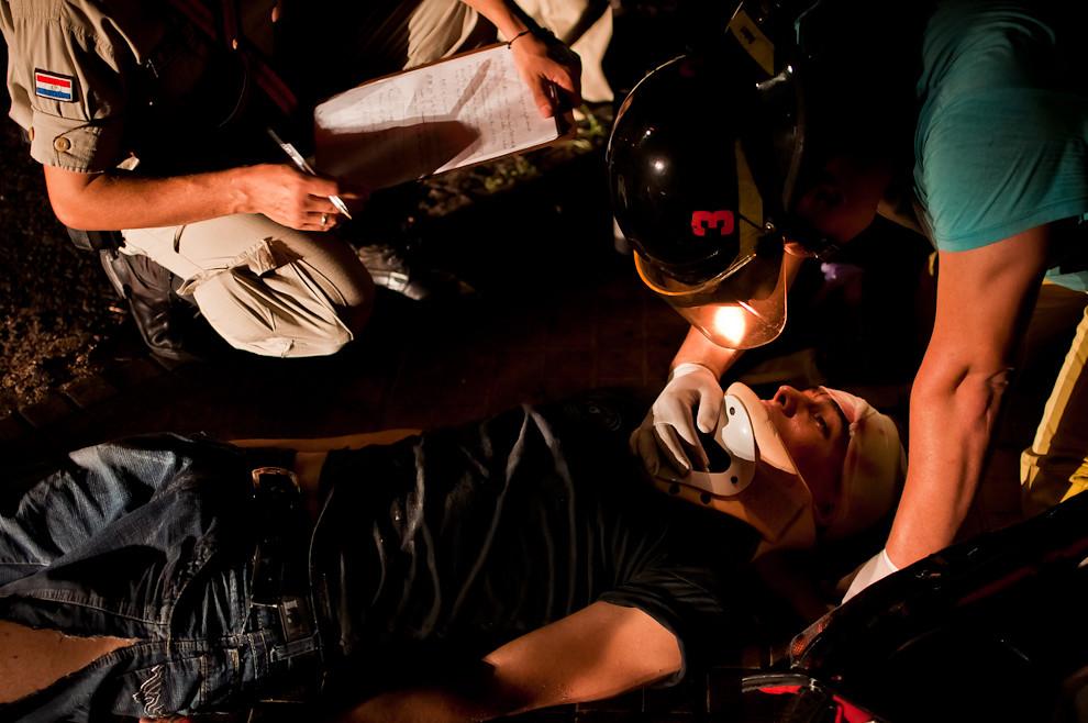Un bombero voluntario mantiene quieta la cabeza de una víctima de accidente de motocicleta mientras llega la ayuda. Sucedió en un violento accidente registrado  en las calles 4ta y Oleary del centro de Asunción. En dicho accidente dos personas salieron gravemente heridas, se necesitó el apoyo de una segunda ambulancia de la 5ta. Compañía de Lambaré para el traslado de los heridos al hospital de emergencias médicas. (Elton Núñez)