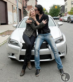 Dmitry and Allison on top of a silver Lexus
