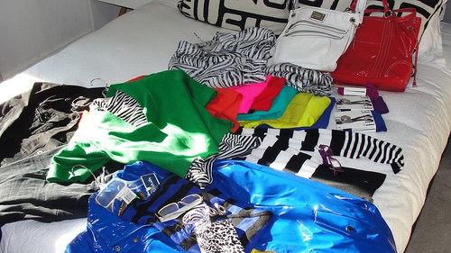 A grouping of garments in pure black, pure white, and strong saturated hues of red, orange, blue, green, yellow and purple, with silver jewelry and black and white accessories
