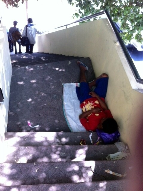 A plastic bottles collector sleeping on the bridge