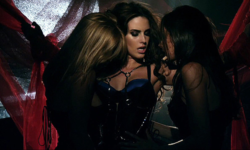 A woman with dark brown hair in a blue bustier is being kissed and touched by two women on either side of her. The woman in the middle looks down, averting eye contact with the camera. The background contains three curtains, two red and one silver, blowing in a breeze.