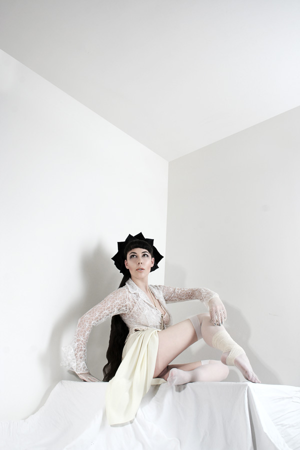 Gestalta photographed by Rebecca Tun. Dark haired woman in a white room