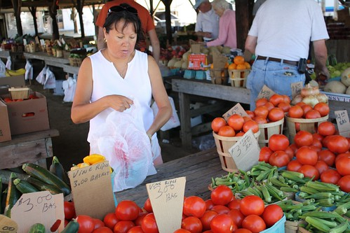 A vendor places tomatoes into a plastic bag for a customer at a Maryland farmers market.  Many beginning producers use farmers markets as the gateway to direct marketing opportunities. Photo by Elvert Barnes