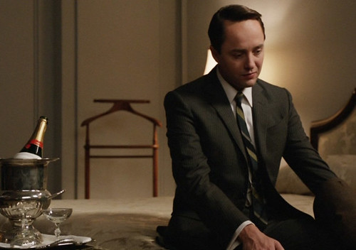Pete Campbell in a hotel room with a bottle of champagne, looking bummed