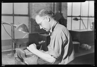 The letterer in the Whitall Tatum mould shop. This man is chiseling out by hand letters in the mould of a bottle, March 1937