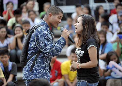 A Sailor sings a duet with a local spectator at Catbalogan Park.