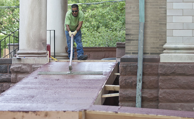 A worker at the Ingersoll House smooths the concrete of the new accesibility ramp on Tuesday, July 24.