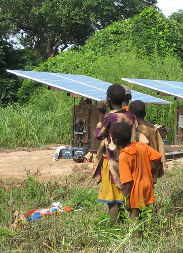 photo of children looking at a solar generator