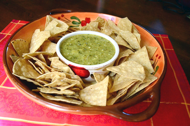 A serving dish with Roasted Tomatillo Salsa in the center surrounded by tortilla chips.