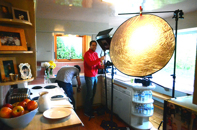 Two guys setting up the kitchen for a video shoot.