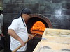A man bakes fresh pita bread during the Olympic event.