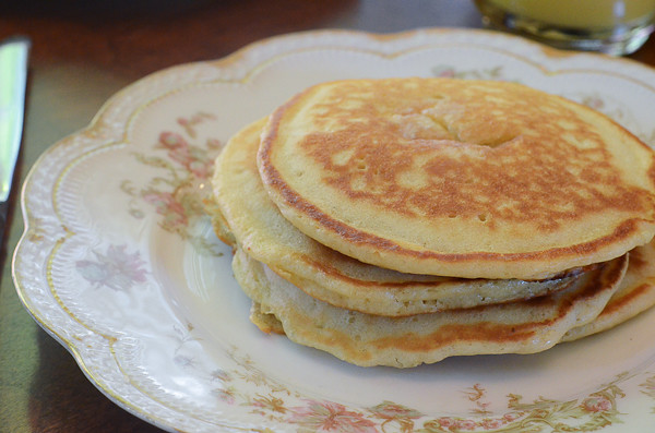 A stack of finished pancakes on a dish.