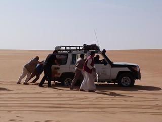 Empujando el todoterreno para sacarlo de la arena en el Desierto Líbico (Egipto)
