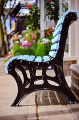 Blue bench on a sunny sidewalk