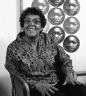 A black and white picture of a middle-aged Catlett. She is seated and looking up at the camera with a bright expression. In the background is one of her prints of the face of a young black boy repeated over and over in circles.