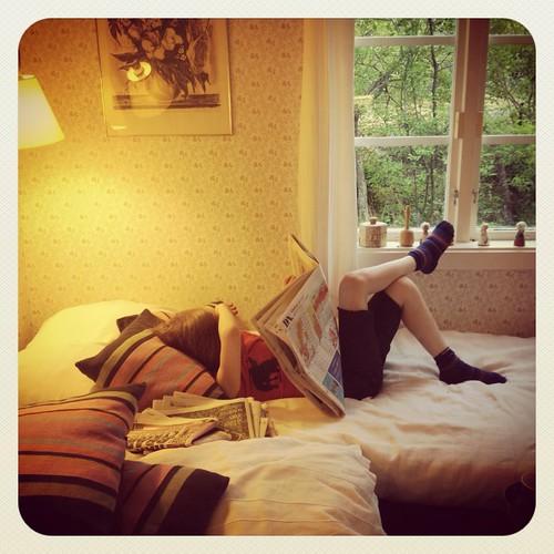 Viggo läser tidningen på morfars säng