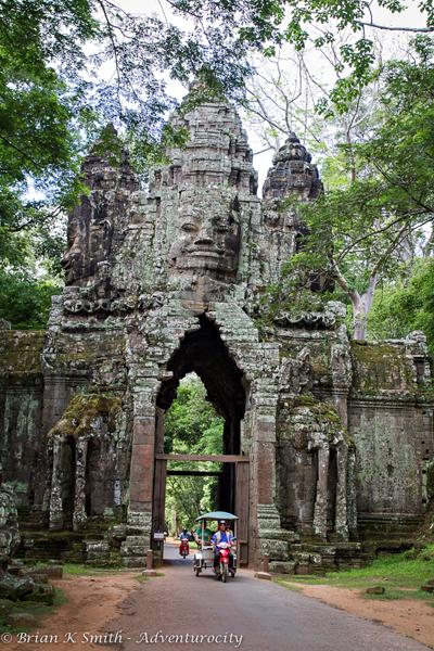 A tuk tuk exits Angkor Thom's South Gate.