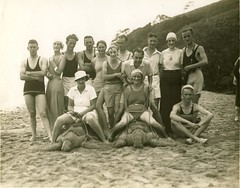 Tourists on a sandy beach, two seated on sea turtles