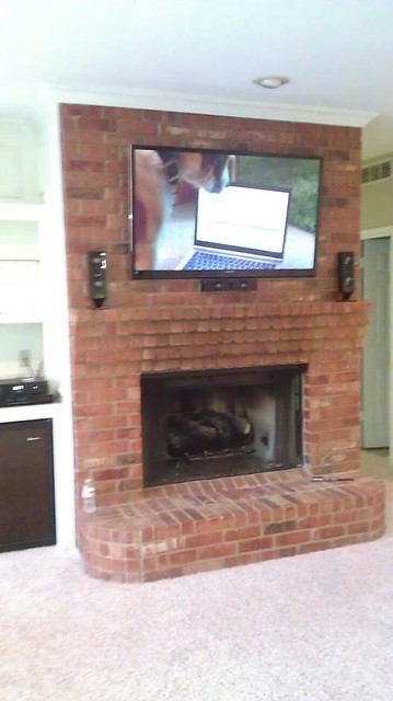 TV Mounted Over Brick Fireplace With Surround Sound