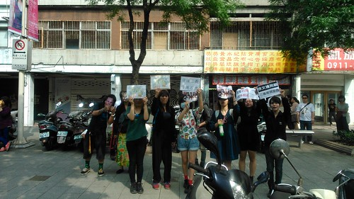 學生舉著標語向遊覽車上的支持民眾表達訴求。攝影:洪郁婷