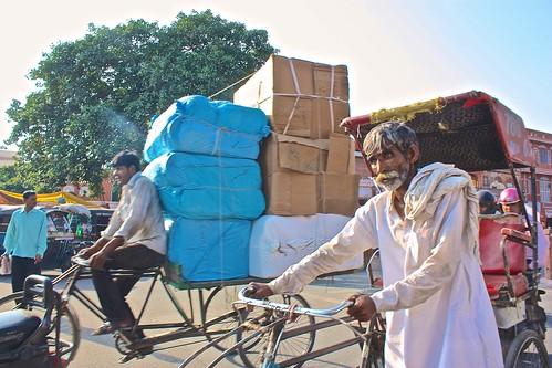 a rickshaw driver pushes his cart