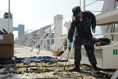 PACIFIC OCEAN (July 27, 2012) – Hospital Corpsman 3rd Class Harry Stege sprays insect repellent on articles of clothing aboard Military Sealift Command hospital ship USNS Mercy in preparation for Pacific Partnership 2012's (PP12) arrival to Cambodia, July 28. (U.S. Navy photo by Mass Communication Specialist 3rd Class Clay M. Whaley/Released)