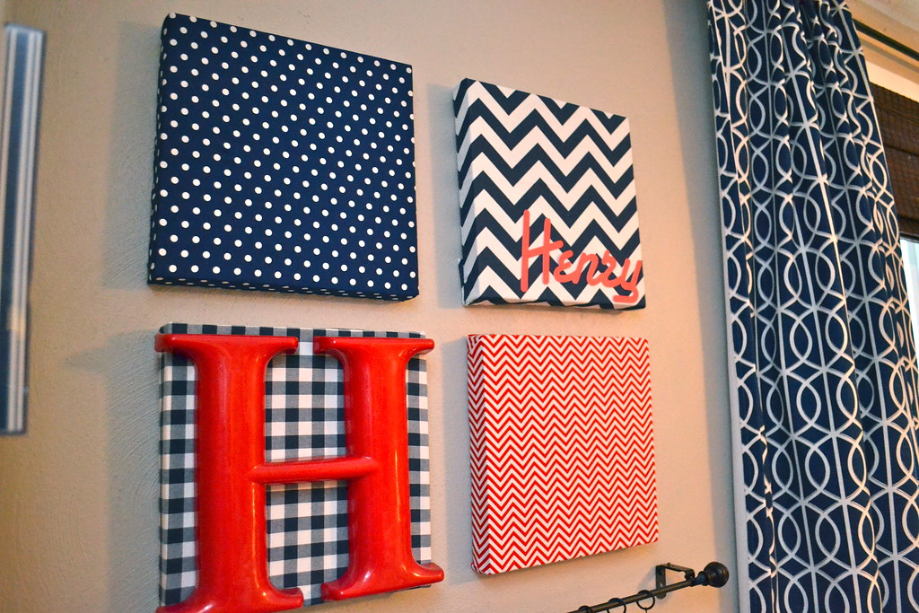 Fabric-covered canvas nursery art and hanging diaper organizers ...