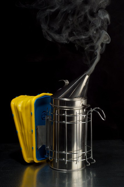 A photo of a vee hive smoker on black background