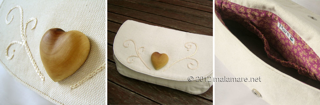 ivory cotton fabric clutch bag with olive wood heart and hand embroidered swirls motif inside view and details