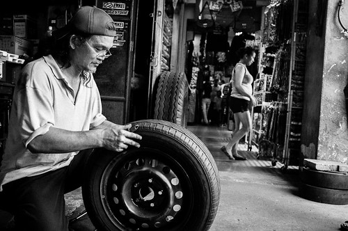 Man fixing tire at Little India, Singapore