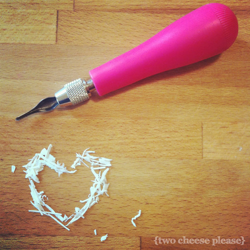 rubber shavings in the shape of a heart with a carving tool above