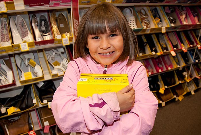 A young student receives a new pair of shoes thanks to the generosity of LANL employees, through the LANL Laces Program
