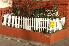outdoor structure(0.0), baluster(0.0), handrail(0.0), gate(0.0), iron(0.0), home fencing(1.0), shrub(1.0), wall(1.0), picket fence(1.0), wood(1.0), brick(1.0), brickwork(1.0),