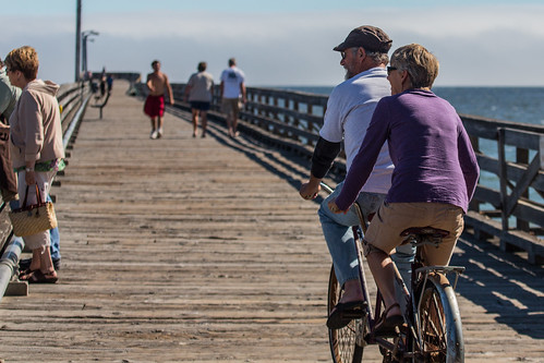 Mature couple, man and woman, peddle a two-person tandem, double bike on the Cayucos Pier.