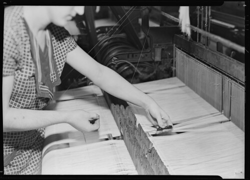 Threading broken warp thread through the eyes of drop wires, preparatory to tying the broken ends, March 1937