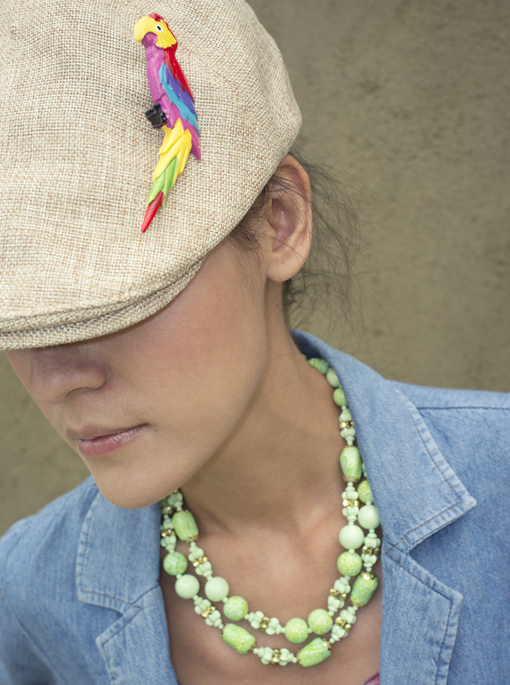 The accessories say it all. Polly's Got A Cracker brooch pinned on a hat, and bright green 1960s beads.