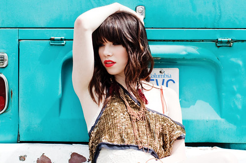 Carly Rae Jepsen poses in front of a funky turquoise car