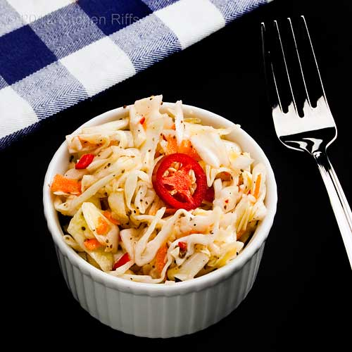 Garlic Coleslaw with Red Jalapeño Pepper Garnish in White Ramekin on Black Background