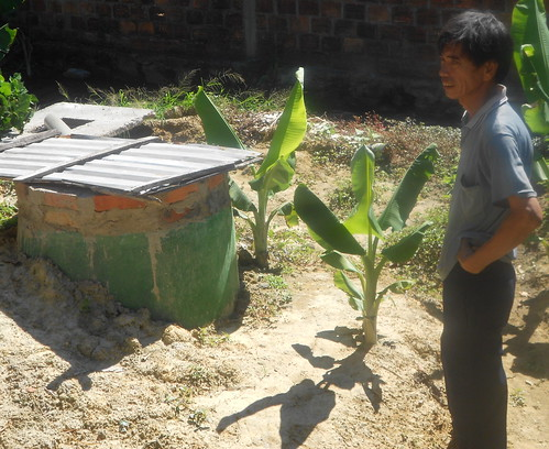 Mr. Dao Van Thuan stands next to the biogas tank in his backyard