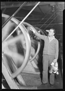 Glass wool. Frederick and Dimmock Co. This shows the worker drawing the glass which he has brought from the other side of the room over on a wheel, March 1937