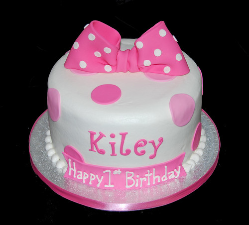 pink polka dot first birthday cake for a minnie mouse celebration